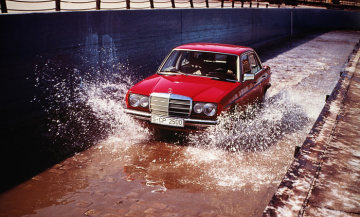 A Mercedes-Benz 123-series Saloon drives through a water basin on the test track at the Untertürkheim plant.