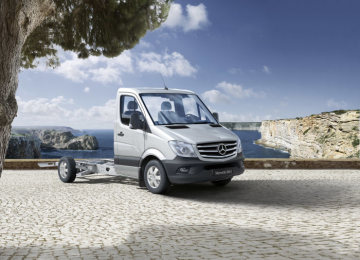 A 3/4 frontal view of a Sprinter with a low-frame chassis for mobile home conversions, brilliant silver metallic