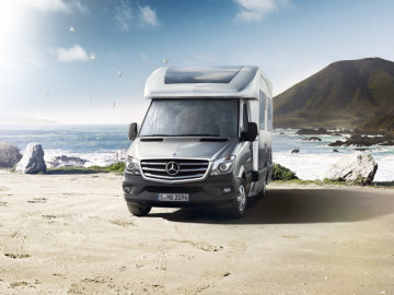 A 7/8 frontal view of a Sprinter chassis with an integrated body for mbile home comversions, brilliant silver metallic