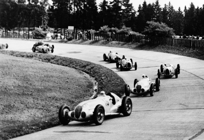 German Grand Prix at Nürburgring, 25 July 1937. Soon after the start in the south bend, the field is led by Hermann Lang with starting number 16 and the subsequent winner, Rudolf Caracciola, with starting number 12, in the Mercedes-Benz formula racing car W 125. Behind them are Bernd Rosemeyer and Hans Peter Müller, both in Auto Union, followed by Manfred von Brauchitsch (second place), also in a Mercedes-Benz W 125.