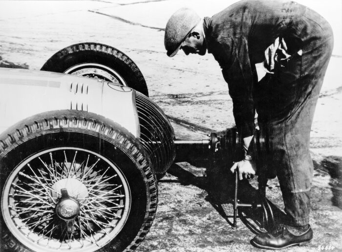 Starting the engine of a Silver Arrow: The mechanic attaches the mobile starter to the W 154. In this case, it was the German Grand Prix on 24 July 1938, a successful first step – Mercedes-Benz posted a one-two finish.