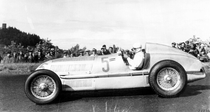 "Rudolf Caracciola is crowned the 1935 European Grand Prix Champion at the wheel of the Mercedes-Benz W 25 formula racing car, which weighed a mere 750 kilograms. The photograph shows the subsequent winner Caracciola at the international ""Eifelrennen"" race at Nürburgring on 16 June 1935."