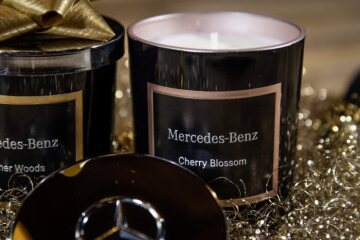 "Scented candles from Mercedes-Benz in ""Cherry Blossom"" and ""Leather Woods"" note. Round glass vessels are double black lacquered. Square frames in metallic colours emphasise the scent and the Mercedes-Benz lettering. The scented candles are closed with a silver lid embossed with the Mercedes star."