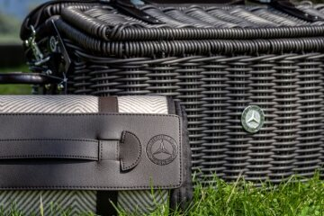 Mercedes-Benz picnic basket and blanket, polyethylene; dark brown. Polyrattan. Leather closures and handles. Reinforced canvas strap. Contents: 2 x cutlery sets, 2 x porcelain plates, 2 x coffee cups, 2 x juice glasses, 1 x pepper shaker, 1 x salt shaker, 2 x napkin 40 x 40 cm, 1 x table cloth 140 x 140 cm. Dimensions approx. 50 x 34 x 31 cm. Blanket of soft polyester fleece with herringbone pattern. Size approx. 140 x 200 cm